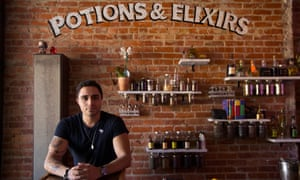 """Co-owner of The Lockhart bar Paris Xerx stands at the wall of ingredients for their """"potions & elixirs""""."""