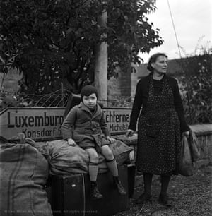 A tired mother and son wait for transport, Luxembourg, 1945