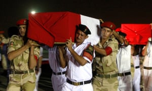 The caskets of policemen killed near the north Sinai town of Rafah are carried after a series of attacks in August 2013.
