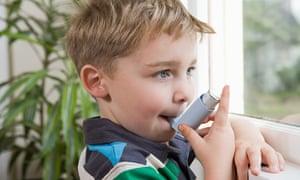 Young boy using asthma inhaler