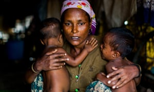 A distressed mother in Sittwe, Myanmar, holds her malnourished twins.
