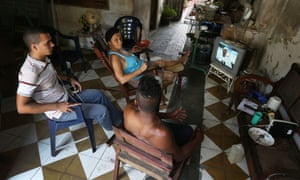 People watch on TV as the Pope arrives in Havana