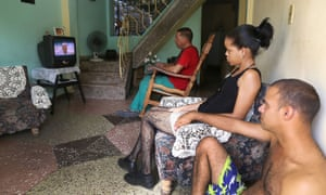 People watch on TV as the Pope arrives in Havana.