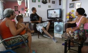 People watch as the arrival of Pope Francis is shown on television in Santiago de Cuba, Cuba.