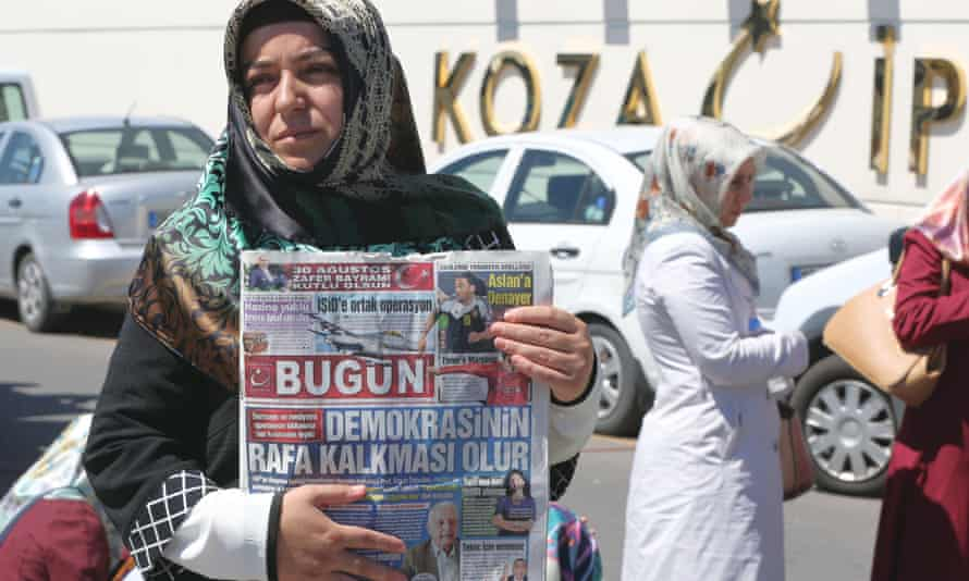 A woman holds a newspaper with the headline 'Operation against the media is the end of democracy' as they protest while police search the premises of the Koza Ipek media group,