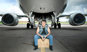Bruce Dickinson sitting in front of a jet plane