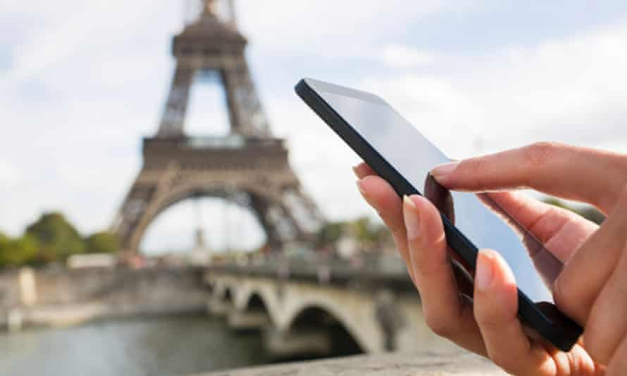 Woman using mobile phone with Eiffel Tower in background