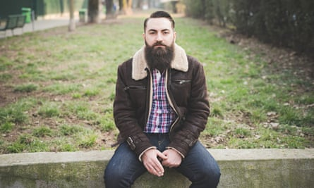 A hipster with a beard in a park