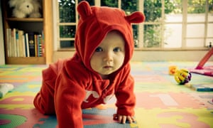 A baby crawling along the floor