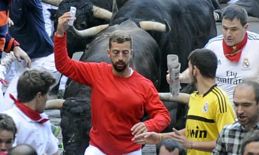 bull runs as man takes selfie