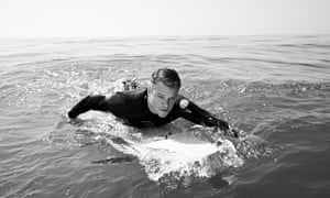 Matt Damon in a wetsuit lying on a paddle board, paddling, in the sea