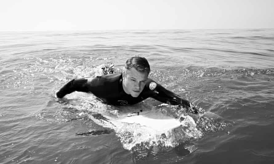 Matt Damon in a wetsuit lying on a paddle board, paddling, in the sea