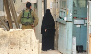 Hadeel al-Hashlamon stands next to a checkpoint in Hebron while a soldier allegedly asks to search her.