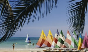 A row of colourful sailing boats lined up on Trelawny Beach, Jamaica