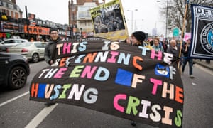 Social housing activists march with a banner stating 'This is the beginning of the end of the housing crisis'.