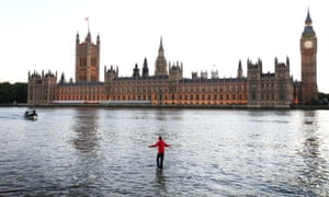 Dynamo walks on water beside the Houses of Parliament.