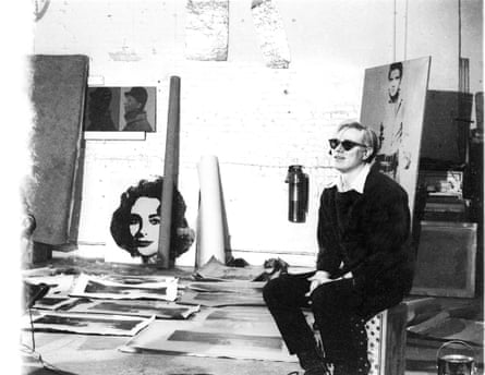 Andy Warhol with silver Liz Taylor, silver Elvis, and Electric Chair paintings at the original Factory studio, 1964.