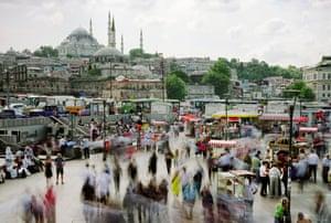 Street vendors and pedestrians mingle beneath the 16th-century Süleymaniye mosque in Istanbul.