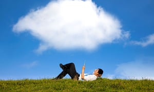 Businessman lying on grass with a tablet