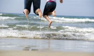 adult and child jumping in sea