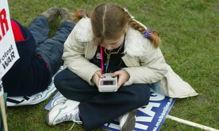 A girl playing a Gameboy during an anti-Iraq War demonstration in London