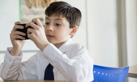 A school boy using his smartphone