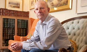 Wilbur Smith sitting on a sofa, leaning with his elbows on his legs