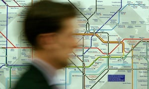 A commuter passes a map of the London Underground system at Westminster tube station.