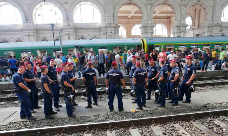 Hungarian police stand in front of people on a platform at the Keleti train station in Budapest.