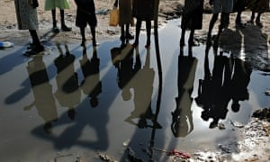 The shadows of Sudanese women and children are reflected in a pool of standing water as they wait at a water distribution point in the village of Guit.