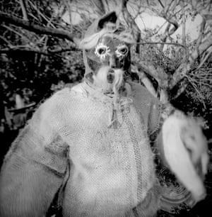 A man wears a tribal mask and hessian costume