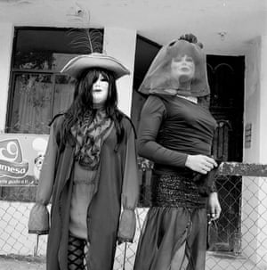 Two women wear white, full-face masks and are dressed head-to-toe in black