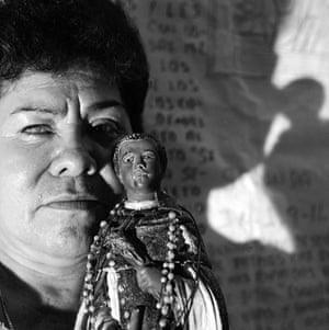 A middle-aged woman holds up a Christian figurine draped in rosaries