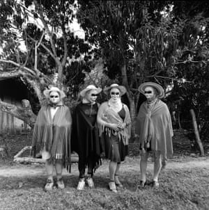 Four women dressed identically in ponchos and sombreros