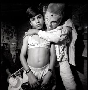 A child with a staring human mask and cape mocks placing an arm around a young girl who looks resignedly to camera