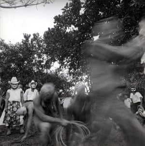 Blurred, demon-like figures dance in a parade through woodland