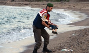A paramilitary police officer carries the lifeless body of Alan Kurdi, three, after a number of migrants died and a smaller number were reported missing after boats carrying them to the Greek island of Kos capsized.