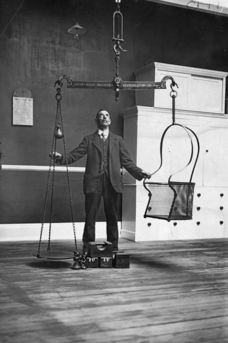 16th June 1924:  A horse racing official testing the scales in the jockey-weighing room in preparation for Royal Ascot.