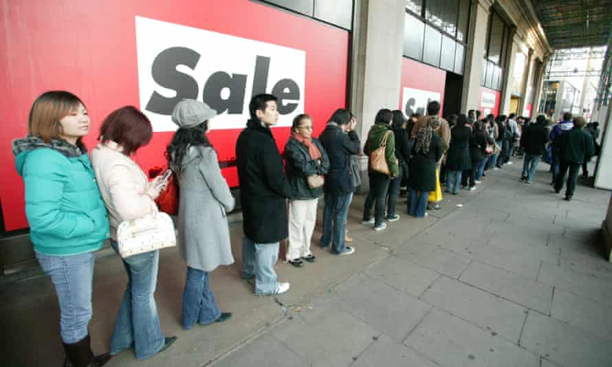Bargain-hungry shoppers queue outside the doors of Selfridges in London
