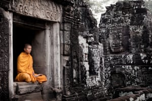 Young monk sits in a temple at Angkor Wat, Siem Reap, Cambodia