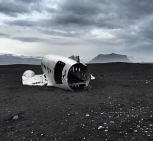 A Douglas Super DC-3 plane lies hollow on a deserted black-sand beach in Iceland