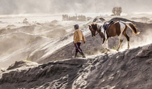 A horse is led away from crowds of people at Mount Bromo, East Java, Indonesia.