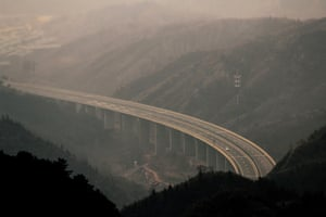 A solitary car on a new highway in a mountainous region north of Beijing, China.
