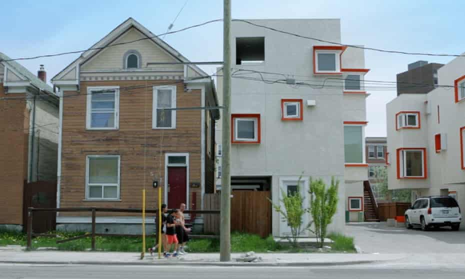 Surreal quality ... the Centre Village project, right, sits next to gabled wood-framed houses more typical of Winnipeg.
