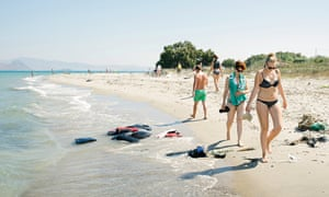 Tourists walk along a beach in Kos