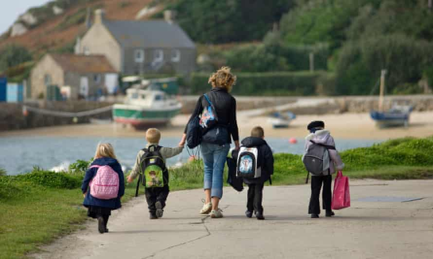 woman and four children walking to school