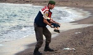 A Turkish policeman holds the body of Aylan Kurdi