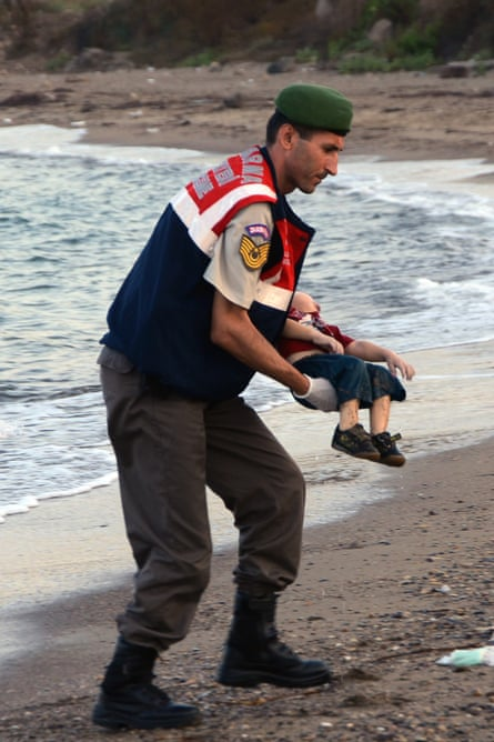 A Turkish paramilitary police officer holds Aylan Kurdi's body