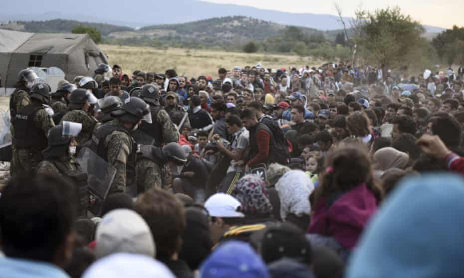 Refugees and migrants wait to pass the borders from the northern Greek village of Idomeni, to southern Macedonia, on 7 September 2015.