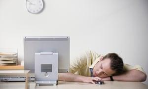 An office worker falls asleep at his desk.
